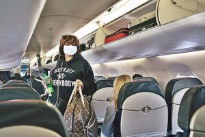 Wearing a face mask, Acquanetta Garth, boards an American Airlines flight to Washington from the Detroit Metropolitan Wayne County Airport in Romulus, Mich., Tuesday, March 3, 2020. (Alyssa Schukar/The New York Times)